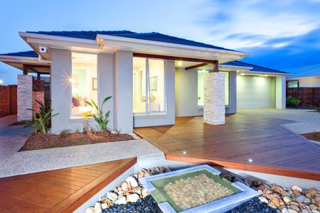 Thsi maison de luxe a des lumières sur l'intérieur et à l'extérieur en raison de l'environnement assombrir. il y a des lumières, même sur le plancher en bois de la façade. Le jardin rempli de pierres avec petit étang d'eau et la couverture de cour en béton par la lumière de la maison Banque d'images - 53755139