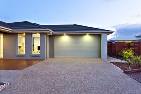 Une partie de cette maison luxueuse comprend un garage avec une porte blanche et éclairé par deux petites lumières sous le plafond.