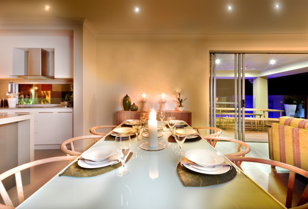 illuminate: House interior has a long table setup including white dishes and wine glasses with wooden chairs ready for the dinner with flashing candles, Flashing candles with small lights on the ceiling illuminated whole area. There is an entrance form the right side