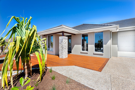 granite: This luxury house has gray walls and a facade with wooden floor. The doorway is in front of the granite stone pillar that holding the roof of the front area. There is a concrete or stone yard, front of the garage next to the veranda. A small tree with a l