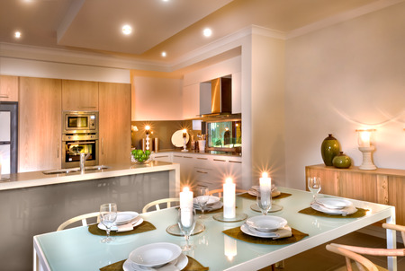 dining table and chairs: Modern kitchen and the dining room with white candles everywhere, wine glasses and dishes on the table, there are wooden chairs around the table, room ceiling has small lights but candles illuminated all over the area. Stock Photo