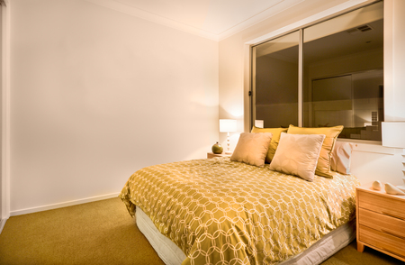 king size: Huge yellow color bed with sheet included white color pattern, there are four pillows in white and yellow. Two wooden cupboards on both sides and conch shells with table lamps on it. There is a shiny antique vase corner of the room, yellow color light ill Stock Photo