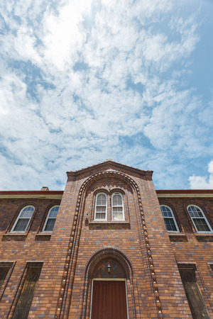 townhomes: Facade of a brick convent building with mixed windows, of wood and glass, squared and round respectively