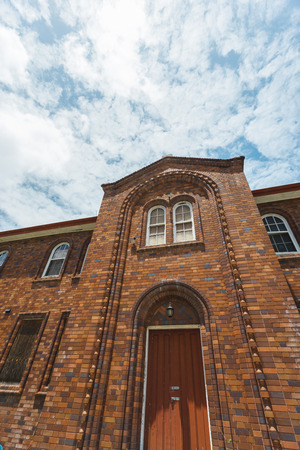 townhomes: Facade of a brick convent building with a chair in the round-arched door