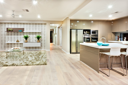 describes: The view of the image describes how the kitchen and living rooms looks like in a luxury house and both can see in the same place. There is wool carpet on the floor with tables and sofas in living side, also there are white countertop with chairs and a fri