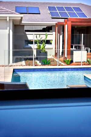 モダンな家とパティオ エリアとスイミング プールはガラスの窓から見ることができる、プール エリアをカバーするガラス パネル、椅子と木製柱外