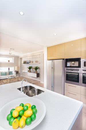 washstand: Luxurious kitchen in the house. There are fruits on the plate like lemon near to the faucet and the washstand top of the white worktop, The refrigerator and the oven with pantry cupboards mount to the wall. There is well decorated room next to the cuisine