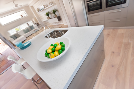 washstand: Green and yellow lemon Isolated on a white dish on the white table, counter top made of ceramic or stone near a silver sink, fruit in the modern kitchen, The plate is very thick, There is a silver faucet fixed to the washstand and small blue dishes near t