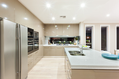 vertical fridge: Indoor of the luxury kitchen includes a fridge and wall ovens with cabinets around the kitchen. The countertop made in ceramic has a silver sink and tap. There is a fruit with a white plate and other blue dishes on the top. There are a long vertical windo Stock Photo