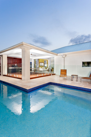 Close view of a modern swimming pool with a dark colored light spread to the water in the evening or dawn. Sky has a light area in the corner over the house roof and mostly dark with small clouds that gives a nice look. The room in front of the pool has i