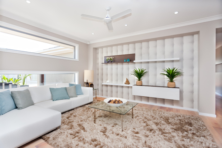Modern living room has a wooden floor with a fur carpet, There are some fancy items on a white plate top of a glass table, white sofas with light blue and gray pillows from the left side near to long windows, ceiling has small lights and a fan in the midd Banco de Imagens