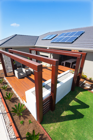 Exterior relaxation area of a luxury hotel with huge wooden pillars and beams, This patio has a wooden floor and short and fat white wall. There is a lawn with a right side and a small track with plants. This modern home has solar panels on the roof, over