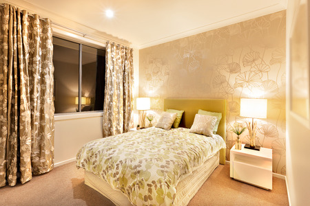 illuminated wall: Beautiful bedroom in a luxury hotel or house illuminated wall with two table lamps made of wood on the white table. The bed is wide huge and well prepared. The dark color curtains are over the window. Bed sheet has an art of flowers and vines, the floor i