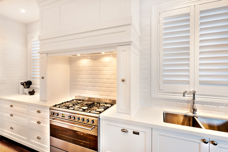 Electrical automatic coocking gas with chimney on top in a kitchen with white walls