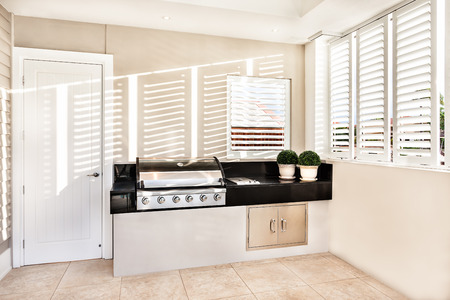 window grill: Electrical automatic cooking gas in kitchen with two flower pot kept on slab and window open with sunlight falling inside of a luxury house