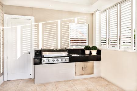 ventana abierta interior: gas de cocina automáticas eléctricas en la cocina con dos maceta de flores mantuvo en la losa y la ventana abierta con luz solar que cae dentro de una casa de lujo Foto de archivo