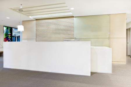 Modern ontvangstbalie of gebouw met lichten aan en witte muren Stockfoto