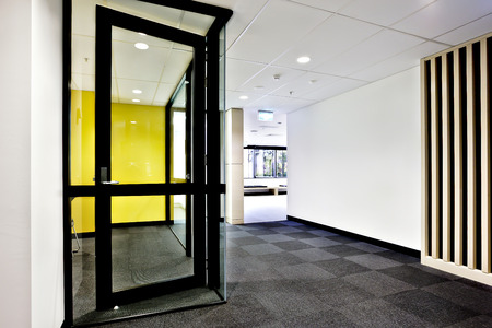Modern office or apartment area through the hallway with glass doors opened and lights on Фото со стока