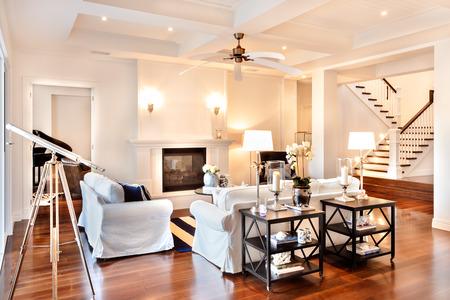 Schöne Salon mit glänzenden Holzboden und Teleskop am Fenster und weißen Sofa