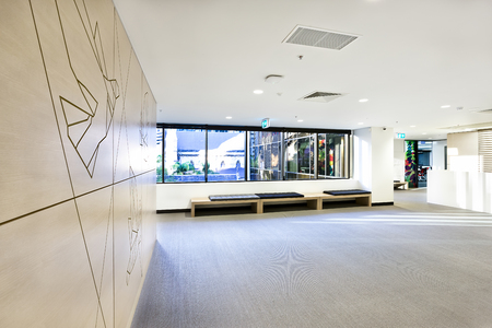 showed: Empty waiting room with space and windows showed outside over the benches and hallway from the side