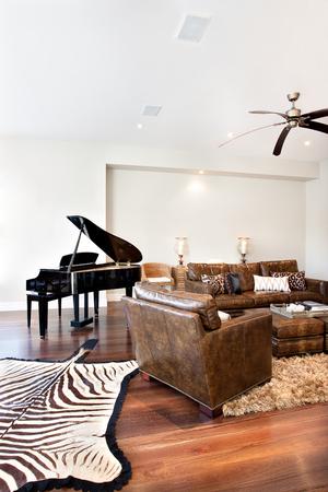 美しいソファ テーブルとピアノのゼブラ プリント カーペット高級住宅の応接室で 写真素材