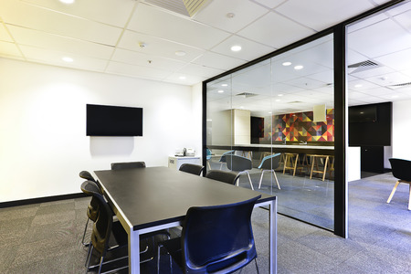 corporate office: Modern meeting room with huge glass door opened and covered with glass walls, including tv and black tables Stock Photo