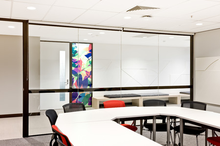 round chairs: Modern conference room with round white table and chairs next to glass wall Stock Photo