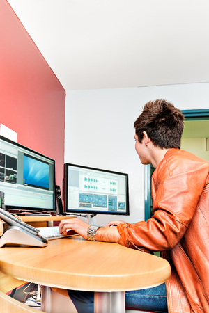 private room: Young guy operating a computer with two screens in a private room and smiling