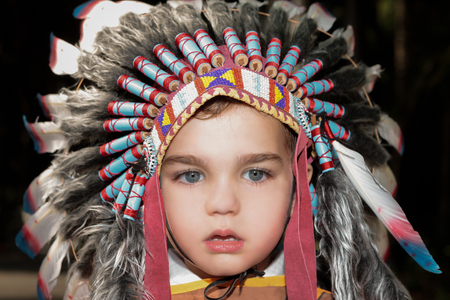 eyes looking up: a close up of beautifull  kid wearing barbarian hat with blue eyes looking into the lense,background view is black.