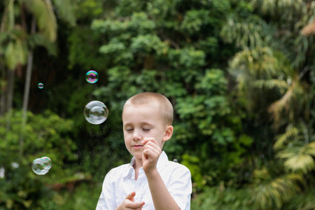 eye closed: A boy wearing white t-shirt with his eye closed playing with bubbles, background view is blur