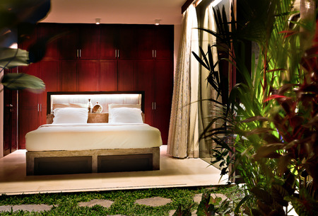 seminyak: Illuminated bedroom at night near the garden that covers tress in a modern house