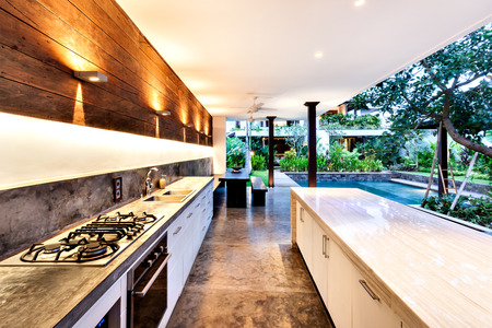 kitchen counter top: Outdoor kitchen with a stove an countertop next to garden including a pool in luxury hotel or house