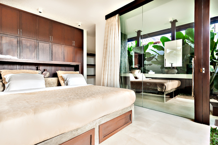 inside of a modern bedroom with glass doors and windows exposed to the outside Banco de Imagens