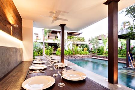 屋外のダイニング エリアは、木製のテーブルや、プール、家の近くにワイングラスの横に白いプレートなどのクローズ アップ