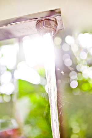 blending: Low angle of a working faucet dropping the water in the sunlight and blending it nicely