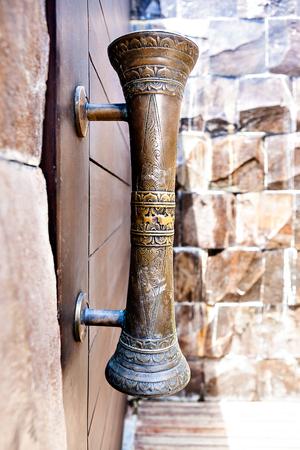 Het oude kijken messing deurkrukken met een grot op de houten deur in de buurt van een stenen muur Stockfoto - 59747399