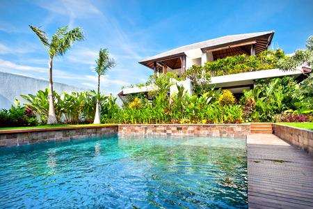 緑の植物庭園とモダンなホテルの前で太陽の光に輝くモダンなスイミング プール