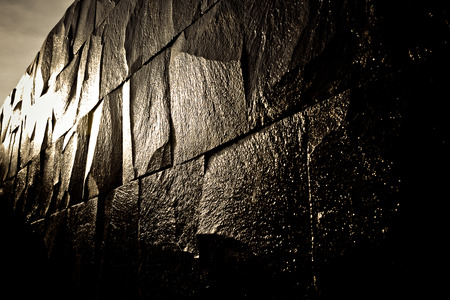 seminyak: Dark stone wall shining with the light and giving the reflection wet appearance Stock Photo