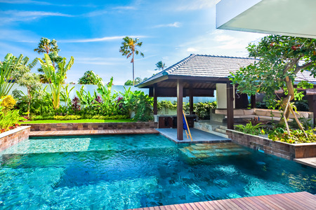 Colorful swimming pool with clear and blue water in a hotel with an outside patio area and a wooden pathways cover with the garden