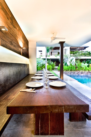 seminyak: Outside dining area with wooden tables and ceramic dishes, The area illuminated by the sunlight and other lightings Stock Photo