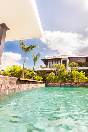 seminyak: Modern swimming pool with a luxury house or hotel with clear water surrounded by stone walls next to the garden with ornamental plants Stock Photo