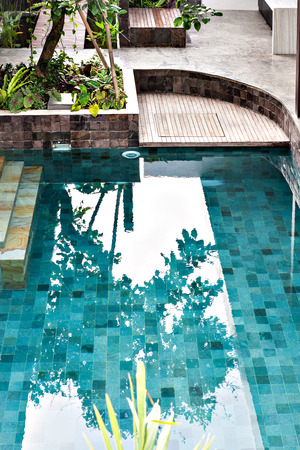 seminyak: Clear swimming pool with still water in a garden with trees