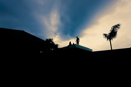 stoop: People on the roof in a dark environment with light sky