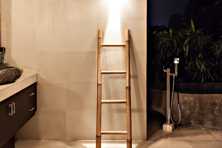 backstairs: Bamboo ladder near the wall in a washroom beside garden with illumination at night