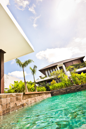seminyak: Modern swimming pool closeup with house or hotel with clear water pond in a garden under the blue sky Stock Photo