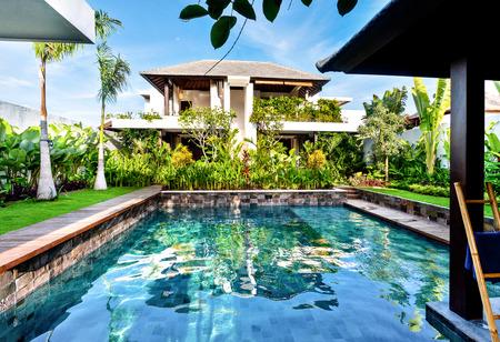 青い空の下、緑豊かな庭園とモダンな家の光に輝く豪華なスイミング プール 写真素材