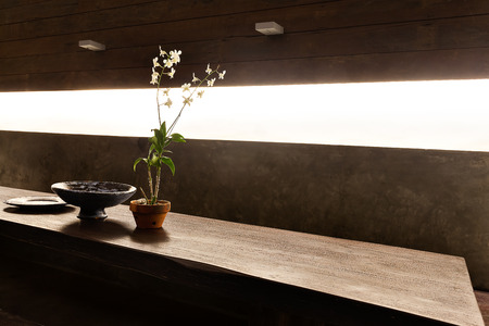 seminyak: Flowering plant in a vase and other fancy items on the wooden table and illuminated from sunlight through the window