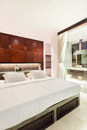 cupboards: Modern bedroom at night illuminated with flashing lights over the glass wall next to the bed with huge and white mattress and pillows beside a brown color wooden cupboards Stock Photo