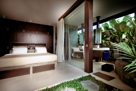 master bedroom: Wooden decorated bedroom attached to the outside area included outdoor washroom naturally decorated and covered with plants and leaves Stock Photo