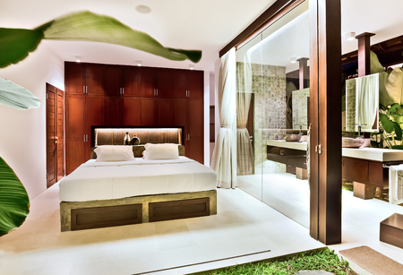 washroom: Luxury bedroom with the natural decor design including lawn, leaves, glass wall next to  washroom in a house Stock Photo